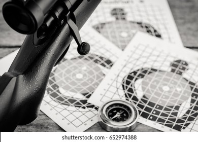 sniper rifle gun with paper target on wooden background ,monochrome filter