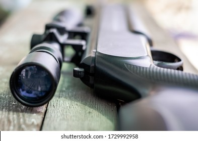 Sniper rifle lies on a wooden background. Optical sight close-up. The concept of hunting.