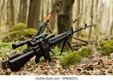 Sniper rifle on bipod on ground background