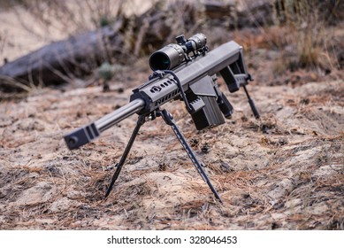 Sniper rifle on bipod with scope on ground background