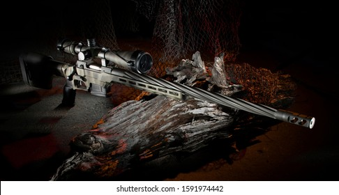 Sniper rifle and rifle scope behind a log with netting to hide the position