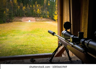 Sniper rifle with silencer and scope at shooting range