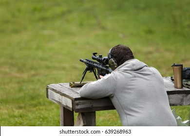 The sniper rifles his rifle and prepares for a shot in the forest on the table