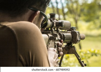Sniper shooting rifle by looking through a scope.