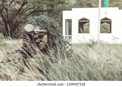 Sniper in urban combat training. Full ghillie camo suit and a high power sniper rifle. In urban combat training ground. Aiming his weapon.