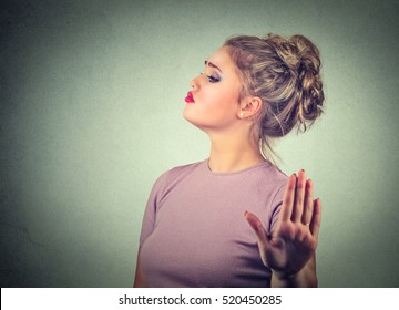 Snobby young annoyed angry woman with bad attitude giving talk to hand gesture with palm outward isolated grey wall background. Negative human emotion face expression feeling body language