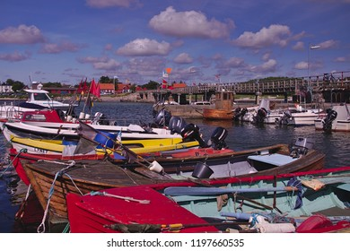 Snoegebek, Bornholm, Denmark - Summer 2017 - a colorful view over ther Harbour of the Little town Snoegebek with fishing motor boats and a cloudy blue sky