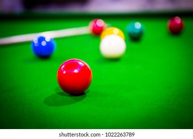 Snooker ball and cue on green snooker table / Red ball focused