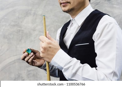 Snooker player standing waiting hold his cue stick and chalk prepare for his turn during competition match