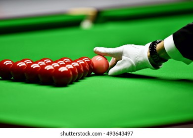 Snooker referee arranging pink ball at the beginning of a game