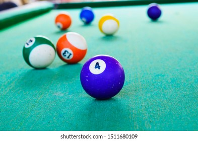 A snooker table with balls spread all over the green colored top