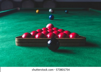 A snooker table with billiard balls and a cue