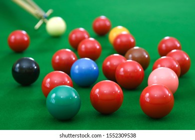 Snooker table with group of balls and rest stick