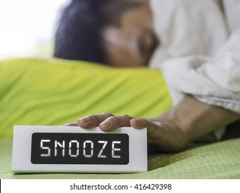 Snooze on digital clock with man hand pressing clock