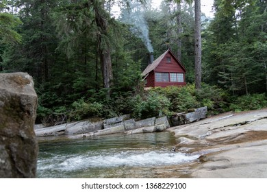 Snoqualmie Washington circa April 2019 a cozy red cabin with smoke from chimney next to a small river viewed while hiking in nature.
