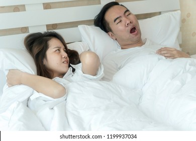 Snoring Asian man and young Asian young woman. Couple sleeping in bed. Young girl can't sleep because of her man's snoring. Man snoring while his wife is covering ears with the pillow.