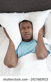 Snoring, insomnia, bad sleep, loud neighbors. Upset tired young african american man freaking out, covers his ears with pillow so as not to hear noise in bedroom, vertical, top view, copy space