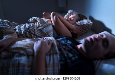 Snoring at night. Sleep apnea. Frustrated annoyed sleepless woman covering ears with pillow in bed. Wife staying awake. Husband asleep. Loud noise. Noisy man. Irritated sleepy lady.