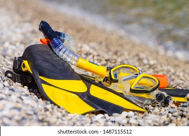 Snorkel equipment flippers and snorkeling mask tube lying on stone beach sea shore. Summer vacation swimming fun concept.