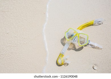 Snorkel equipment snorkeling mask tube lying on stone beach sea shore. Summer vacation swimming fun concept.