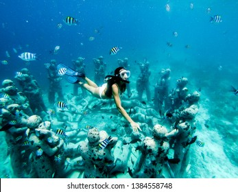 Snorkel woman swimming in a turquoise ocean under the flooded statues. Life tours and outdoor water sports. The concept of free diving.