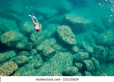 A snorkeler explores the scenic rock formations of the islands of Lake Malawi, Malawi, Africa.