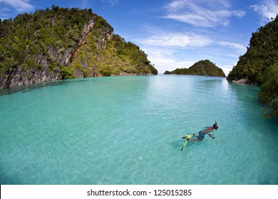A snorkeler explores a shallow channel of clear water between two limestone islands near Misool, Raja Ampat, Indonesia.