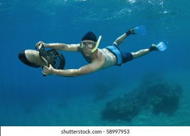 snorkeler rides underwater scooter