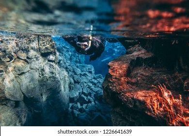 Snorkeler Snorkeling swimming diving in the blue cold glacier water in famous fissure Silfra between two tectonic plates in the national park Thingvellir in Iceland. Blue transparent water deep colors