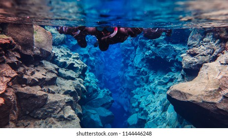 Snorkeler swimming in the glacier cold fissure in Silfra Thingvellir National park in Iceland between two tectonic plates with transparent crystal clear blue water