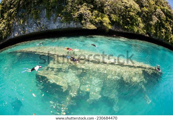 Snorkelers swim above a shipwreck in Palau's inner lagoon. Palau harbors dozens of shipwrecks, most of them sunk during World War II.