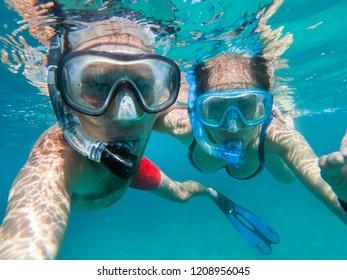 Snorkeling couple in love taking selfie underwater in Maldives