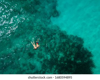 Snorkeling couple in the middle of the Indian Ocean, coral reefs, green water, from high above. Birds eye view.