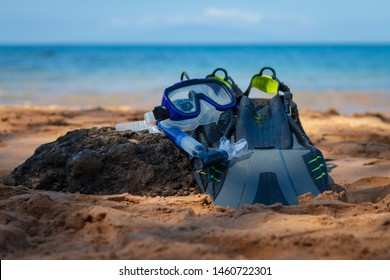 Snorkeling equipment consisting of snorkel, diving goggles and flippers Snorkeling equipment lying on a beach