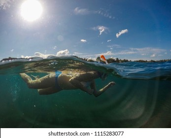 Snorkeling girl in sunny tropical seashore. Woman swim in blue sea. Snorkeling girl in full-face snorkeling mask. Split landscape above and below waterline. Active vacation on seaside underwater photo