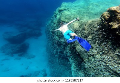 Snorkeling man swimming underwater in blue sea water