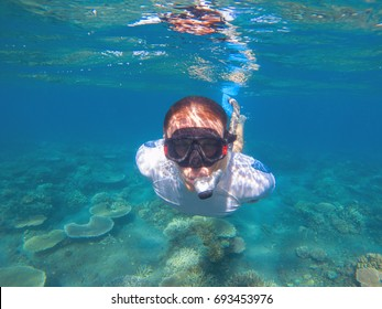 Snorkeling man underwater portrait. Male snorkel in tropical lagoon undersea photo. Swimming in coral reef. Tropical sea activity. Water sport. Exploring tropical coral reef. Man in snorkeling mask