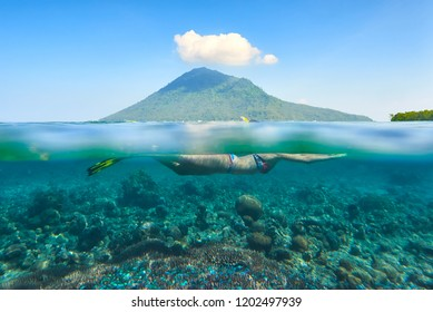 snorkeling over a beautiful coral reef in the background the island of Manado Tua, North Sulawesi. Indonesia.
