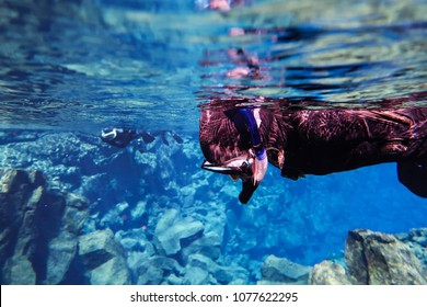 Snorkeling and scuba diving in popular touristic Icelandic fissure Silfra, blue underwater lava rocks