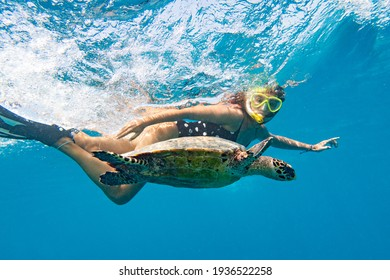 Snorkeling with a sea turtle. Girl swimming with a mask next to the turtle, Maldives
