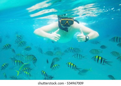 Snorkeling in Thailand. Man underwater shows ok thumbs up. Active travel and leisure