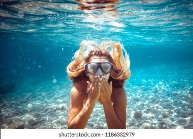 Snorkeling woman blowing a kiss underwater in the tropical sea