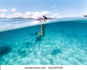 Snorkeling woman exploring beautiful ocean sealife. Water sport outdoor activities. Swimming and snorkeling on summer holidays. Under and above water photography.
