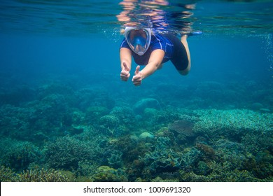 Snorkeling woman in full face mask. Underwater coral landscape and snorkel. Female swimmer in snorkeling mask. Woman learning to swim. Tropical vacation activity. Water sport. Seashore vacation