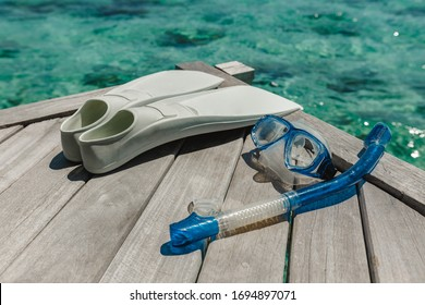 Snorkelling equipment on wood background. Flippers, mask and snorkel top view image. diver eyeglasses, diving goggles, snorkel and fins on the jetty