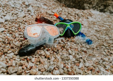 Snorkelling masks on pebble beach. Two diving masks and snorkels with drops of water washed by sea waves.