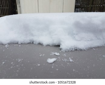 snow accumulated on a table with a while building and wood fence in the background