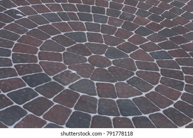 Snow adds to circular design pattern of sidewalk made of gray and maroon concrete brick pavers