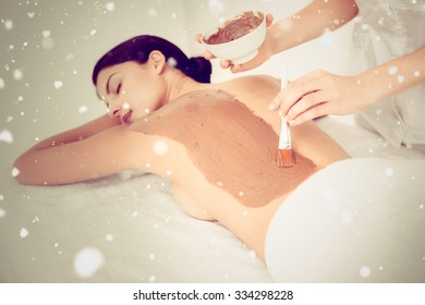 Snow against beautiful brunette enjoying a chocolate beauty treatment