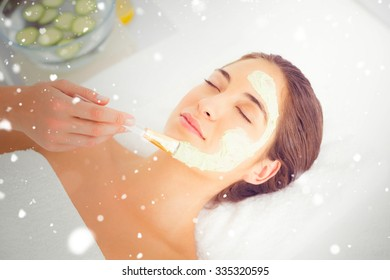 Snow against beautiful brunette getting a facial treatment